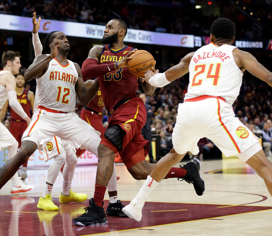 . Cleveland Cavaliers\' LeBron James (23) drives against Atlanta Hawks\' Taurean Prince (12) and Kent Bazemore (24) in the second half of an NBA basketball game, Sunday, Nov. 5, 2017, in Cleveland. (AP Photo/Tony Dejak)