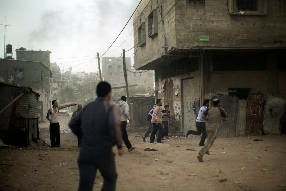 . Palestinians run for cover after an Israeli airstrike hit the northern Gaza City on Nobember 16, 2012. Gaza militants targeted Tel Aviv on November 16, with another rocket, defying Israeli warnings of a possible ground assault to follow its aerial bombardment of the Hamas-run strip. MARCO LONGARI/AFP/Getty Images