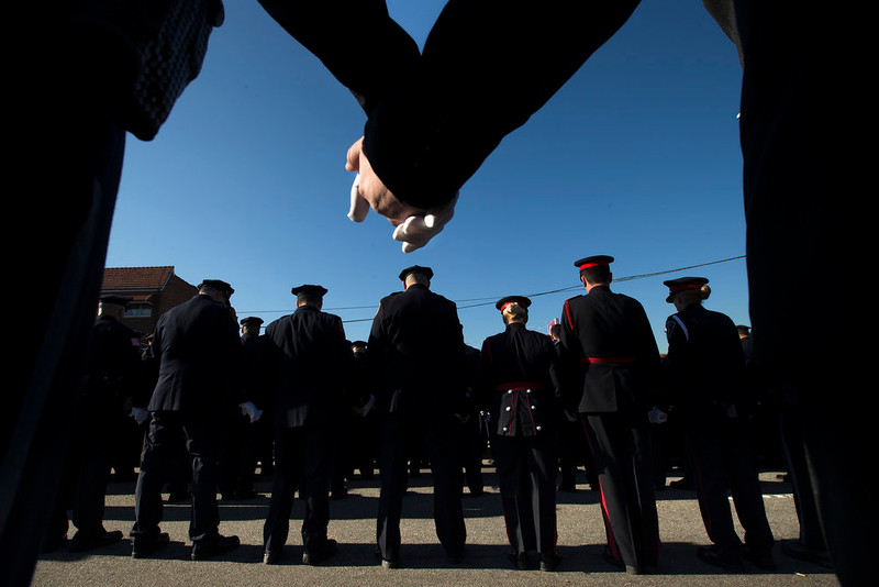 . Police officers hold hands in prayer during the funeral service of New York City police officer Rafael Ramos in the Glendale section of Queens, Saturday, Dec. 27, 2014, in New York. Ramos and his partner, officer Wenjian Liu, were killed Dec. 20 as they sat in their patrol car on a Brooklyn street. The shooter, Ismaaiyl Brinsley, later killed himself. (AP Photo/John Minchillo)