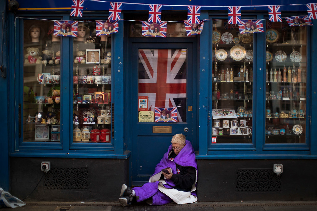 . A woman sits at the door of a closed souvenirs shop, near Windsor castle, England, Friday, May 18, 2018. Preparations continue in Windsor ahead of the royal wedding of Britain\'s Prince Harry and Meghan Markle Saturday, May 19. (AP Photo/Emilio Morenatti)