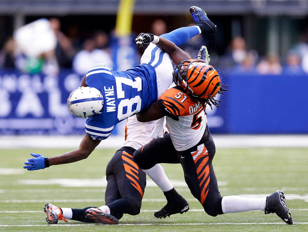 . Indianapolis Colts wide receiver Reggie Wayne (87) is tackled by Cincinnati Bengals linebacker Jayson DiManche (51) during the second half of an NFL football game, Sunday, Oct. 19, 2014, in Indianapolis. (AP Photo/Michael Conroy)