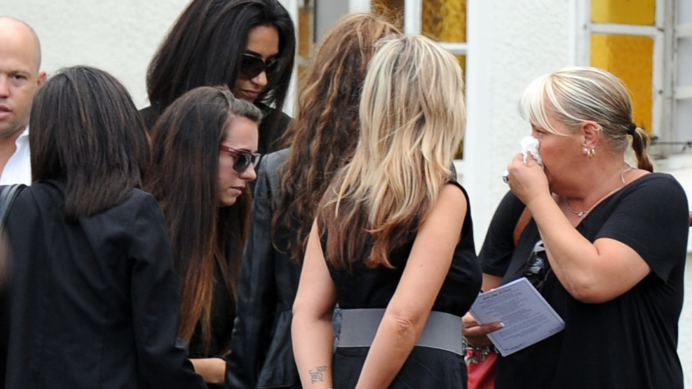 ". Relatives and friends of late South African model Reeva Steenkamp gather during the funeral ceremony at the crematorium building in Port Elizabeth on February 19, 2013. The 29-year-old law graduate and cover girl was gunned down four times on February 14, 2013 at the upmarket Pretoria home of the Olympic and Paralympic star Oscar Pistorius. South African prosecutors on February 19 told a bail hearing that Oscar Pistorius was guilty of ""premeditated murder\"" in the Valentine\'s Day killing of his model girlfriend at his upscale home.  ALEXANDER JOE/AFP/Getty Images"