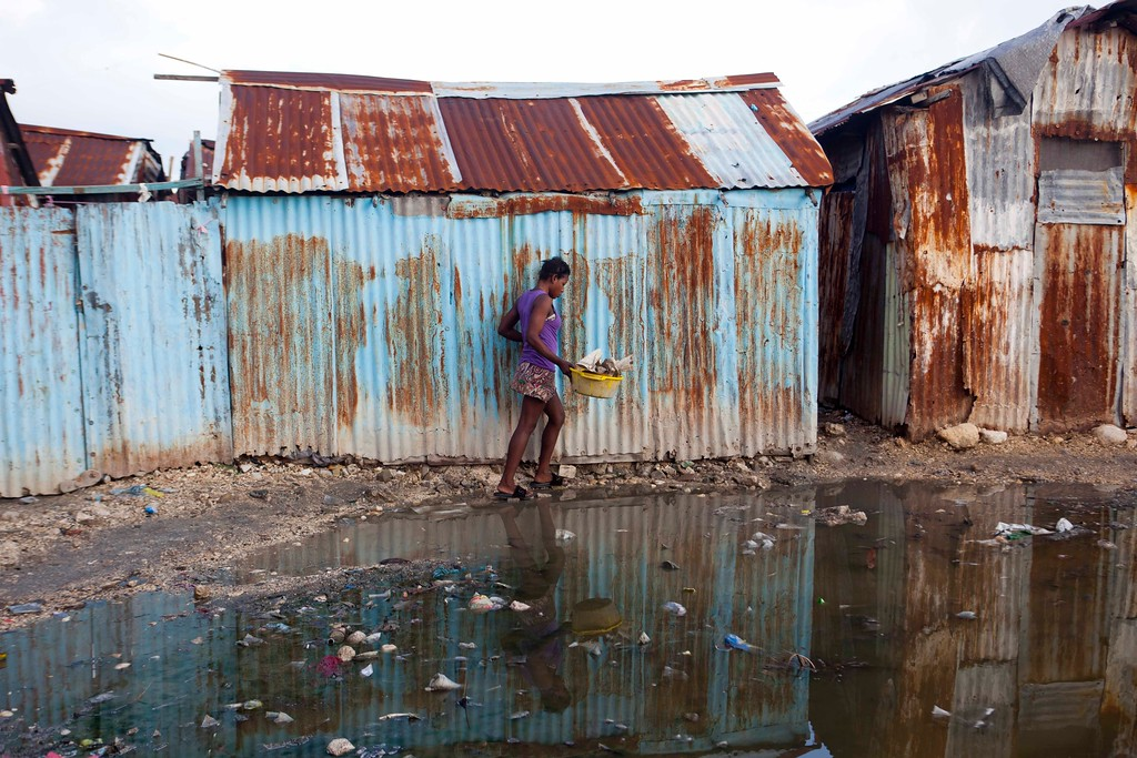 . A woman skirts a puddle as she walks home in the seaside slum of Port-au-Prince, Haiti, Wednesday, Sept. 6, 2017. Heavy rain and 185-mph winds lashed the Virgin Islands and Puerto Rico\'s northeast coast Wednesday as Hurricane Irma roared through Caribbean islands. The northern parts of the Dominican Republic and Haiti could see 10 inches of rain. (AP Photo/Dieu Nalio Chery)