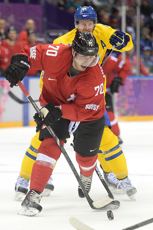 . Switzerland\'s Denis Hollenstein controls the puck against Sweden during the third period of Sweden\'s 1-0 preliminary round group C win at Bolshoy Arena. Sochi 2014 Winter Olympics on Friday, February 14, 2014. (Photo by AAron Ontiveroz/The Denver Post)