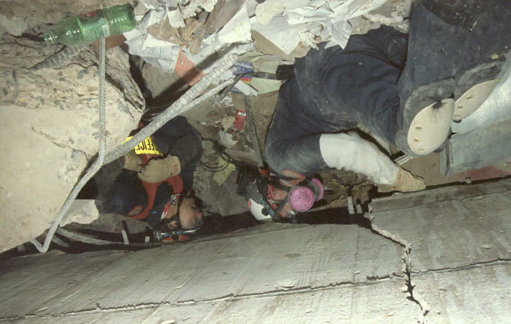 . Rescue workers dig, 29 April 1995, through the ruble of the Federal Building in Oklahoma City looking for survivors of the 19 April bombing. Work was halted during 29 April because of falling debris that was a danger to the rescuers.            Green bottle in upper right of vertical photo. (Roman BAS/AFP/Getty Images)