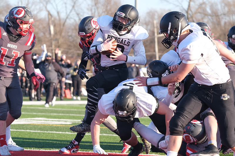 Oak Forest's Tyler Gentile squeezes through the pile of players for the touchdown against Bremen. Friday, April 2, 2021, in Midlothian. (Gary Middendorf/Daily Southtown)