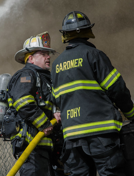 The Hubbardston Fire Chief talks with a Gardner FF while putting water on the remains of a vacant factory.