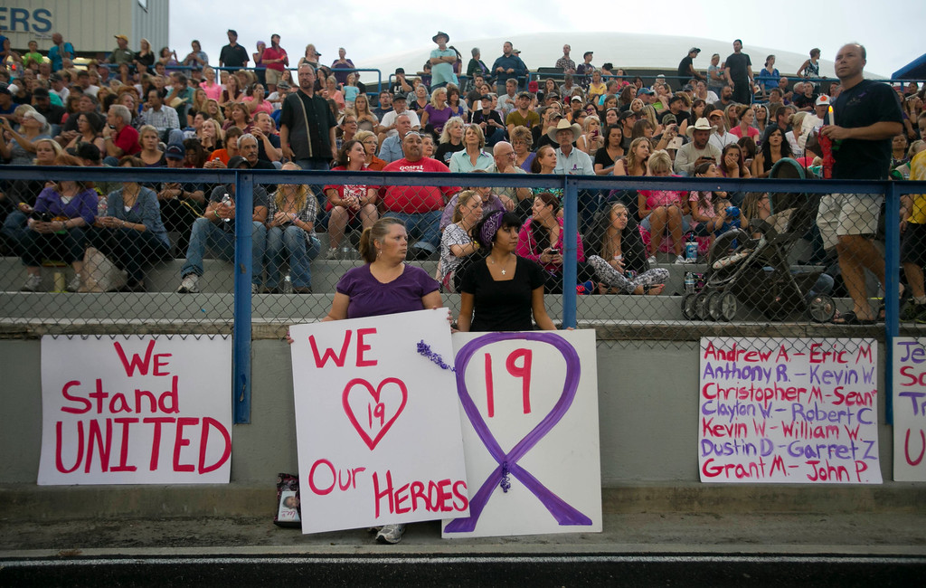 . Donna Chamblee, left, of Dewey, Ariz. and Nicole Fought, 19, of Prescott Valley, Ariz. hold signs during a vigil for the 19 firefighters killed battling the Yarnell Hill Fire, on the football field at Prescott High School in Prescott, Ariz. on Tuesday, July 2, 2013. (AP Photo/The Arizona Republic, David Wallace)