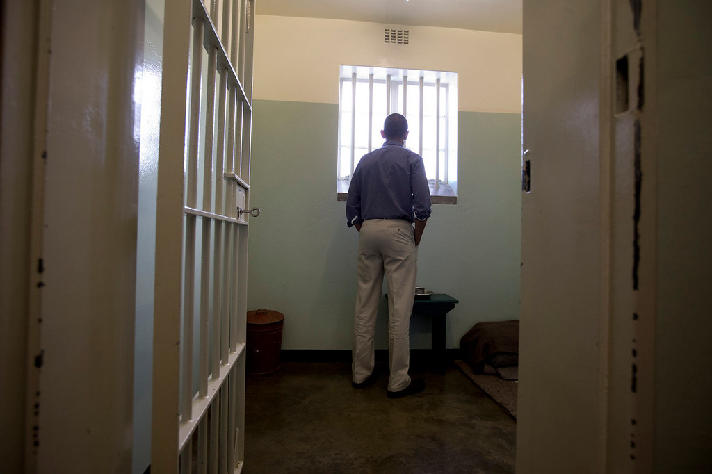 . U.S. President Barack Obama peers out from Section B, prison cell No. 5, on Robben Island, South Africa, Sunday, June 30, 2013.  This was former South African president Nelson Mandela\'s cell, where he spent 18-years of his 27-year prison term locked up by the former apartheid government.  (AP Photo/Carolyn Kaster)