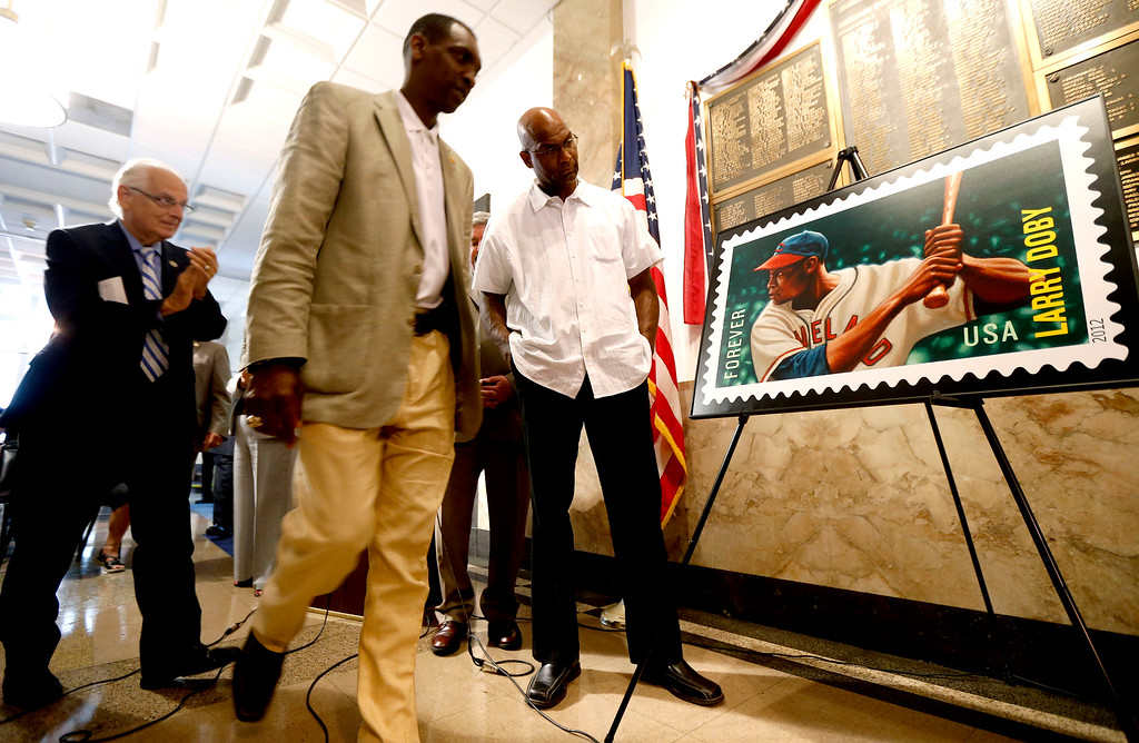 . Larry Doby, Jr., right, the son of the first black baseball player to play in the American League, looks at a commemorative U.S. postage stamp in honor of his father, Larry Doby, Thursday, Aug. 23, 2012, in Paterson, N.J. Standing next to Doby Jr. are congressman Bill Pascrell, left, and Paterson Mayor Jeffery Jones during the stamp release celebration. The South Carolina-born Doby attended Eastside High School in Paterson, where he earned 11 varsity letters in several different sports. The Hall of Famer began his professional baseball career with the Newark Eagles of the Negro National League. After serving in World War II, Doby returned to the Eagles before joining the Cleveland Indians in 1947. (AP Photo/Julio Cortez)
