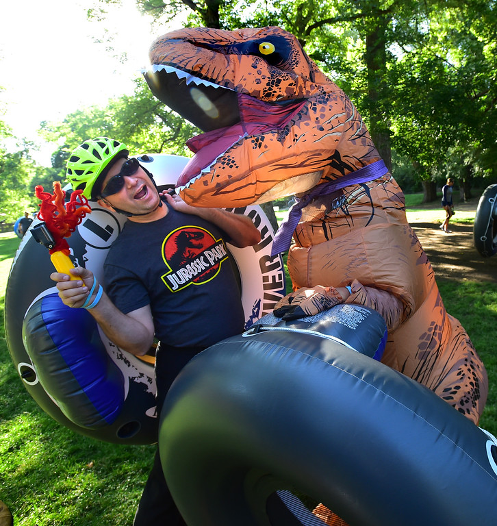 . David Lee, as T-Rex, jokes around with fellow tuber Cliff Crawford as they wait for the start of the 11th Annual Tube to Work Day, in Eben G. Fine Park in Boulder on Wednesday morning.  Paul Aiken Staff Photographer July 11 2018