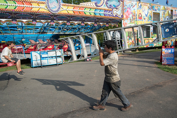 09/11/19 Wesley Bunnell | StaffrrCarnival workers assemble attractions ahead of the Berlin Fair taking place this weekend. A worker carries a ladder past the Himalaya ride.