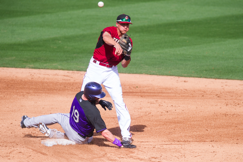 . Nick Ahmed #75 of the Arizona Diamondbacks attempts to complete a double play as Charlie Blackmon #19 of the Colorado Rockies slides into him at Salt River Fields at Talking Stick on February 28, 2014 in Scottsdale, Arizona. (Photo by Rob Tringali/Getty Images)