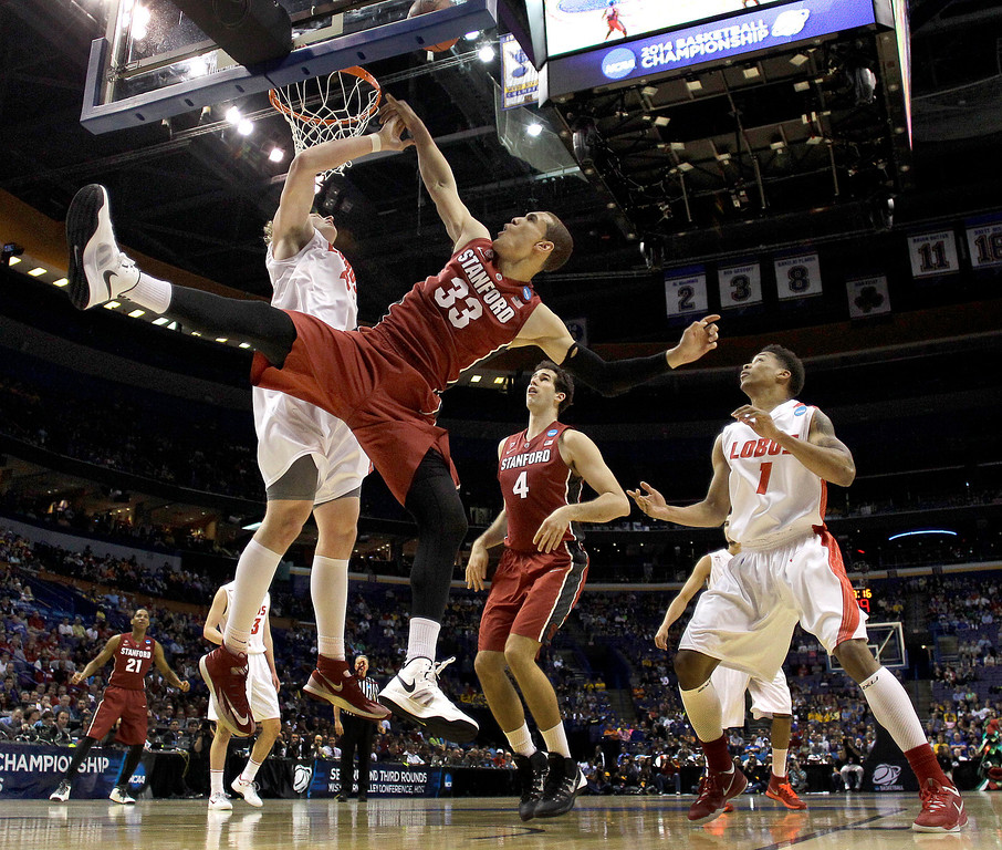 . New Mexico\'s Cameron Bairstow, left, blocks a shot by Stanford\'s Dwight Powell (33) during the first half of a second-round game in the NCAA college basketball tournament, Friday, March 21, 2014, in St. Louis. (AP Photo/Charlie Riedel)