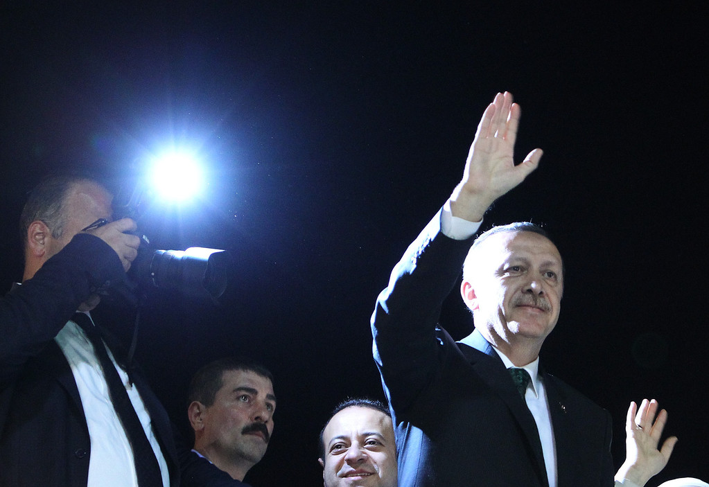 . Turkish Prime Minister Recep Tayyip Erdogan, right, waves to the crowd upon his arrival at the Ataturk Airport of Istanbul early Friday, June 7, 2013. Erdogan took a combative stance on his closely watched return to the country early Friday, telling supporters who thronged to greet him that the protests that have swept the country must come to an end. (AP Photo/Thanassis Stavrakis)
