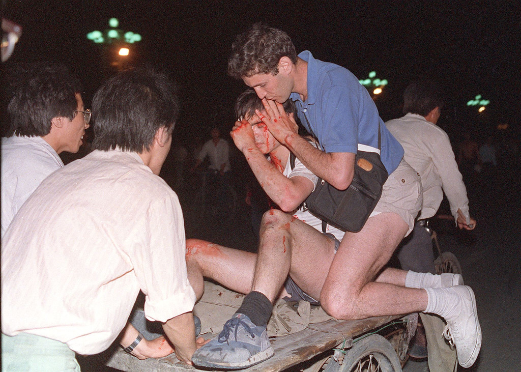 . Taken care by others, an unidentified foreign journalist (2nd-r) is carried out from the clash site between the army and students 04 June 1989 near Tiananmen Square.  (THOMAS CHENG/AFP/Getty Images)