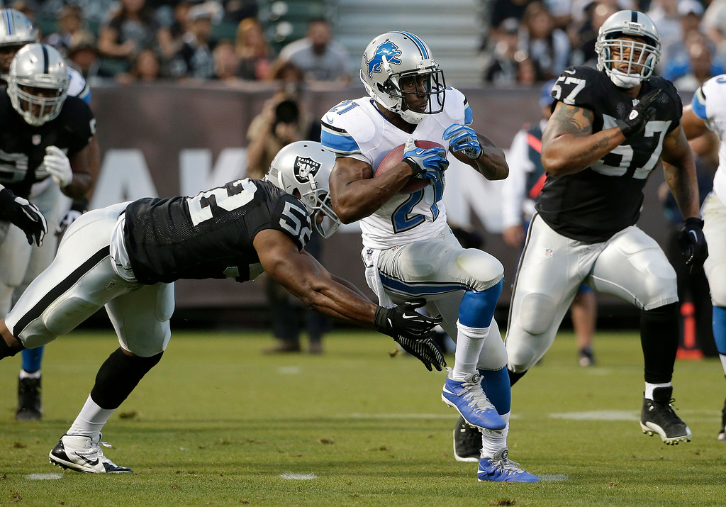 . Detroit Lions running back Reggie Bush (21) runs between Oakland Raiders outside linebacker Khalil Mack, left, and defensive end LaMarr Woodley (57) during the first half of an NFL preseason football game in Oakland, Calif., Friday, Aug. 15, 2014. (AP Photo/Marcio Jose Sanchez)