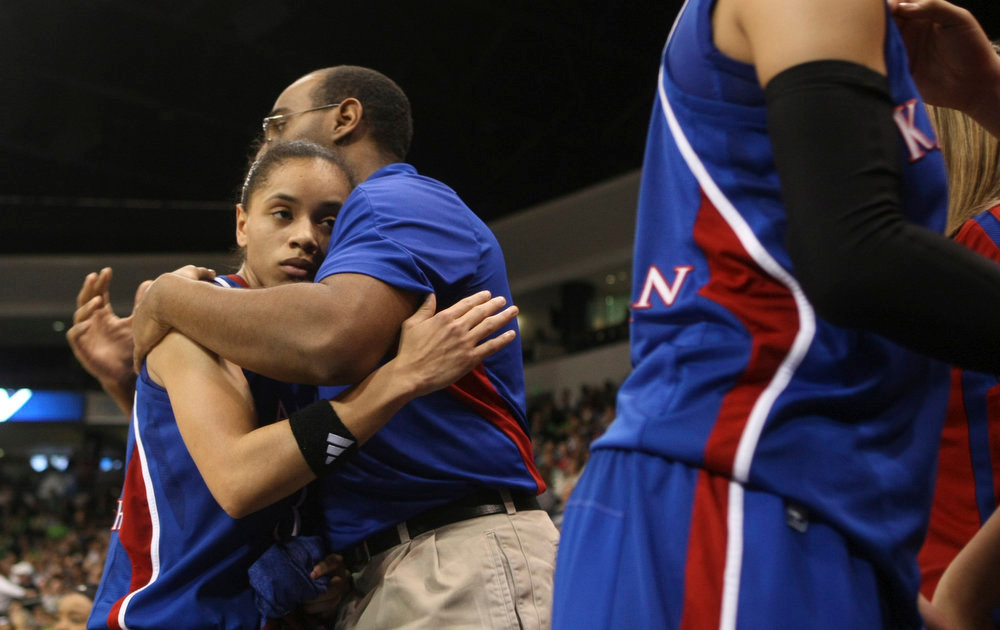 . Kansas guard Angel Goodrich gets a hug form an assistant coach near the end of a regional semi-final of the NCAA college basketball tournament Sunday March 31, 2013 in Norfolk, Va.  Notre Dame won 93-63. (AP Photo/Jason Hirschfeld)