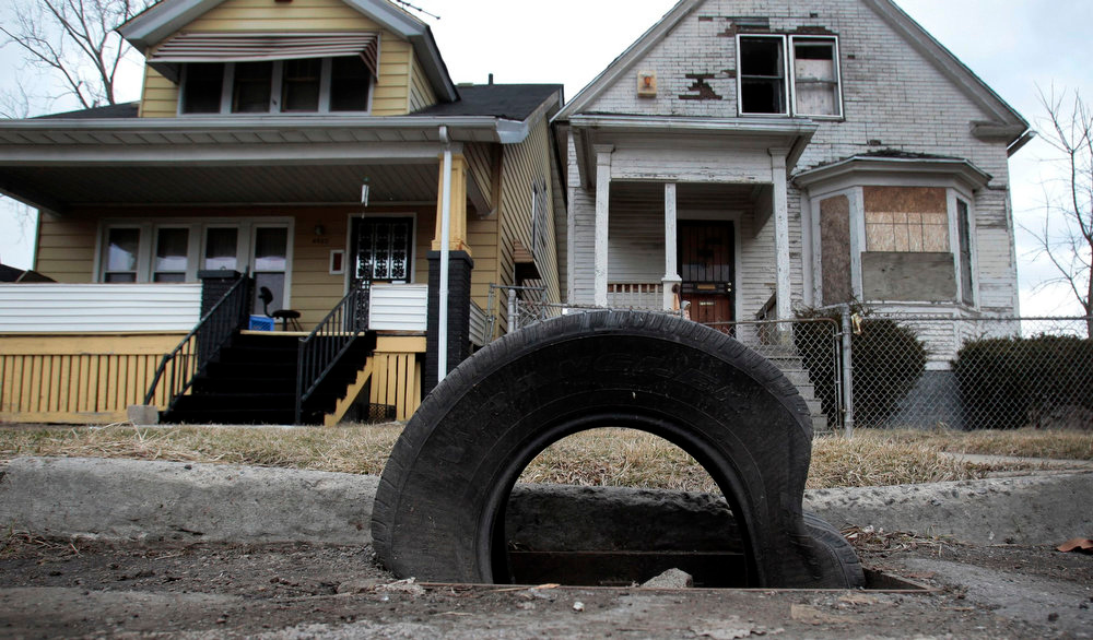 . A tire sits on a storm drain as a replacement for a cast iron grate, stolen for scrap, in front of a well-kept home and vacant home in a neighborhood where many of the grates are missing on the east side of Detroit, Michigan March 19, 2013.  When the state-imposed manager of Detroit, Kevyn Orr, begins the job on Monday he will wade into a city of crumbling neighborhoods where police fail to respond to some calls, arson fires burn out of control, and residents scour charred buildings for scrap metal to sell. Picture taken March 19, 2013.  REUTERS/ Rebecca Cook