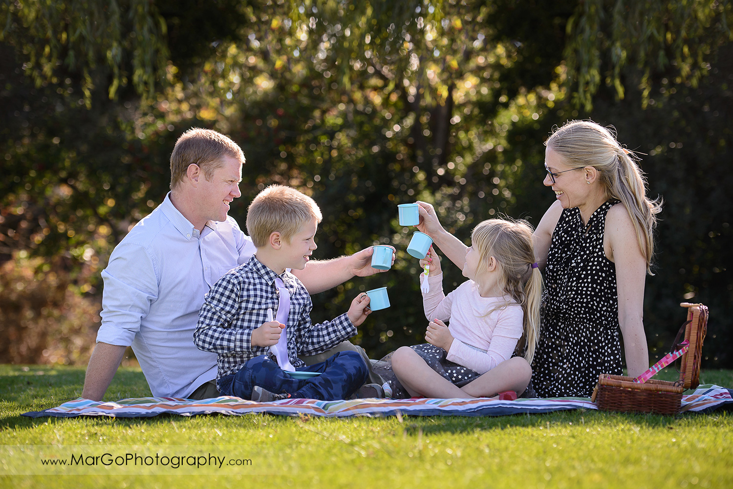 family of 4 dringking tea and sitting on the grass at Mountain View Shoreline Lake Park