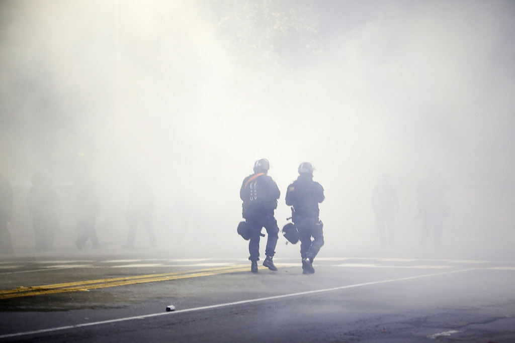 . Two police officers in riot gear walk through a cloud of tear gas during a demonstration over recent grand jury decisions in police-involved deaths on Sunday, Dec. 7, 2014, in Berkeley, Calif. (Stephen Lam/Getty Images)
