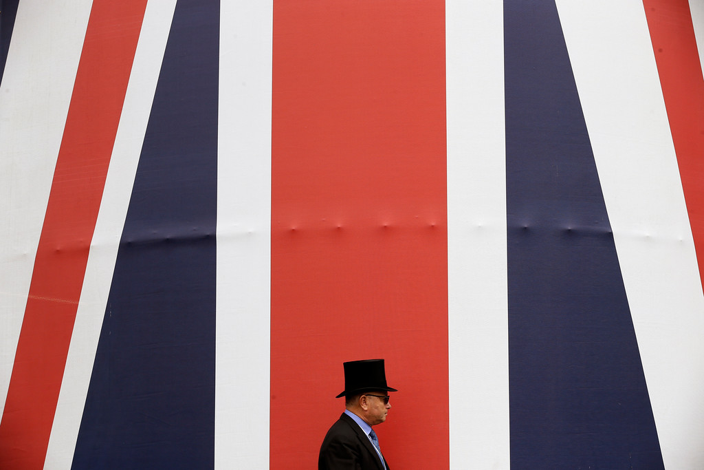 . A racegoer walks past a huge British flag during the second day of the Royal Ascot horse race meeting in Ascot, England, Wednesday, June 20, 2018. (AP Photo/Tim Ireland)