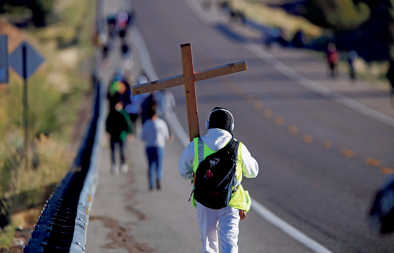 Jose Eduardo Gomez of Denver carried his cross from Cities of Gold Casino during his pilgrimage to the Santuario de Chimayo on Good Friday, April 19, 2019. The cross has friend's names, people's names he knows that are sick and people who need prayers. This is his second year. Luis Sánchez Saturno/The New Mexican
