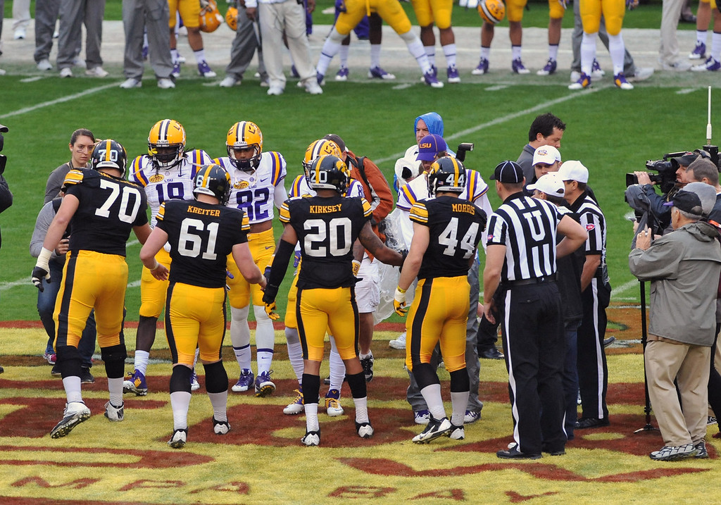 . Captains of the Iowa Hawkeyes and the LSU Tigers meet at midfield for the coin toss before play January 1, 2014 in the Outback Bowl at Raymond James Stadium in Tampa, Florida.  (Photo by Al Messerschmidt/Getty Images)