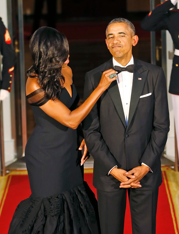 . First lady Michelle Obama, left, adjusts the tie of President Barack Obama as they await the arrival of Chinese President Xi Jinping and his wife Peng Liyuan for a State Dinner at the White House in Washington, Friday, Sept. 25, 2015. (AP Photo/Steve Helber)