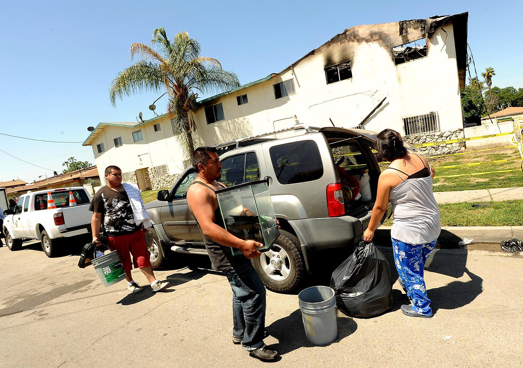 . Residents remove items from their homes in the aftermath of Sunday\'s apartment complex fire in Highland May 13, 2013.  GABRIEL LUIS ACOSTA/STAFF PHOTOGRAPHER.