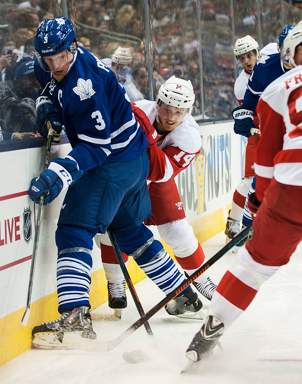 . Toronto Maple Leafs\' Dion Phaneuf (3) battles Detroit Red Wings\' Gustav Nyquist (14) for the puck during first-period preseason NHL hockey game action in Toronto, Friday, Oct. 3, 2014. (AP Photo/The Canadian Press, Aaron Vincent Elkaim)