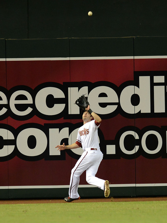 . PHOENIX, AZ - SEPTEMBER 16:  A.J. Pollock #11 of the Arizona Diamondbacks catches a fly ball at the base of the center field wall against the Los Angeles Dodgers at Chase Field on September 16, 2013 in Phoenix, Arizona.  (Photo by Norm Hall/Getty Images)