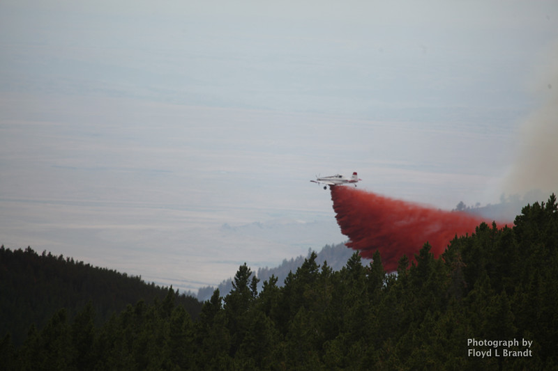 Havre Daily News / Floyd Brandt  With the change in wind direction the fire back track over already burned area between the towns of Landusky and Zortman finding some new fuel in a bowl deep inside the Little Rockies giving the crew a hand to construct fire breaks with the battle going to air power Sunday. Airplanes carrying fire retardant drop it along the ridge of the mountain slowing the fire.