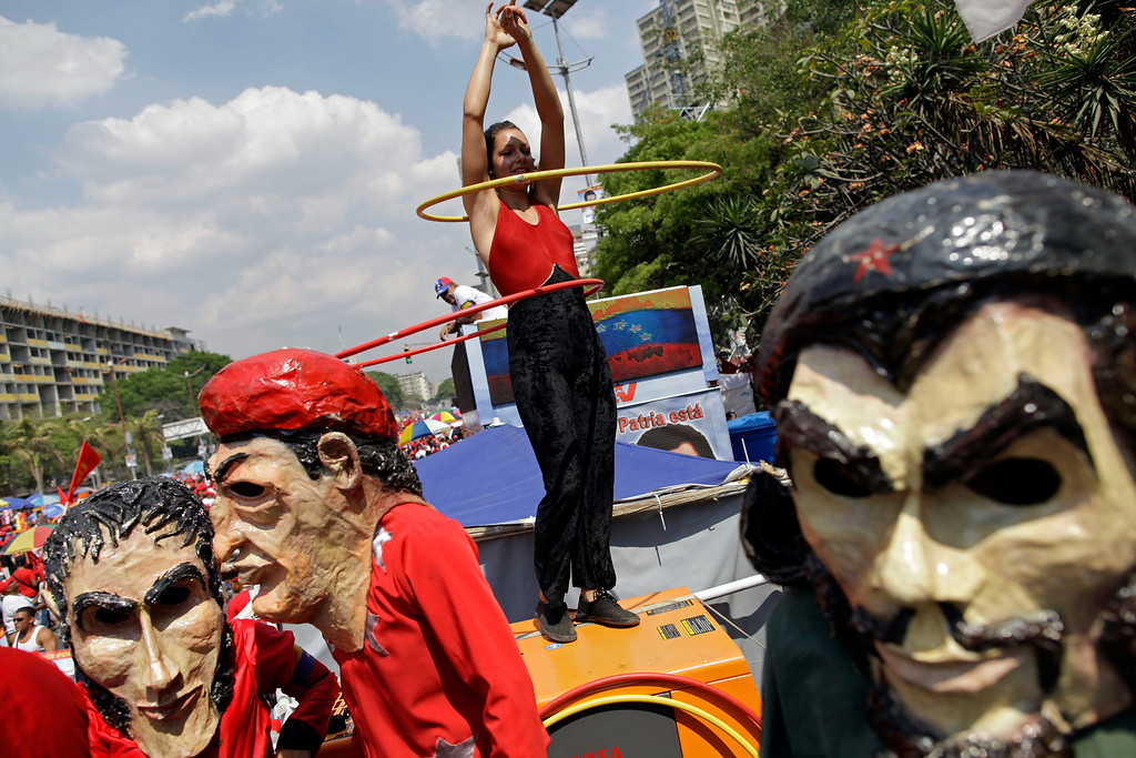 ". Supporters of ruling party presidential candidate Nicolas Maduro dressed as Cuba\'s revolutionary hero Ernesto ""Che\"" Guevara, right, late President Hugo Chavez, center left, and independence hero Simon Bolivar, far left, dance next to a cheerleader on a bus before Maduro\'s closing campaign rally in Caracas, Venezuela, Thursday, April 11, 2013. Maduro, Chavez\'s hand-picked successor, is running for president against opposition candidate Henrique Capriles on April 14. (AP Photo/Enric Marti)"