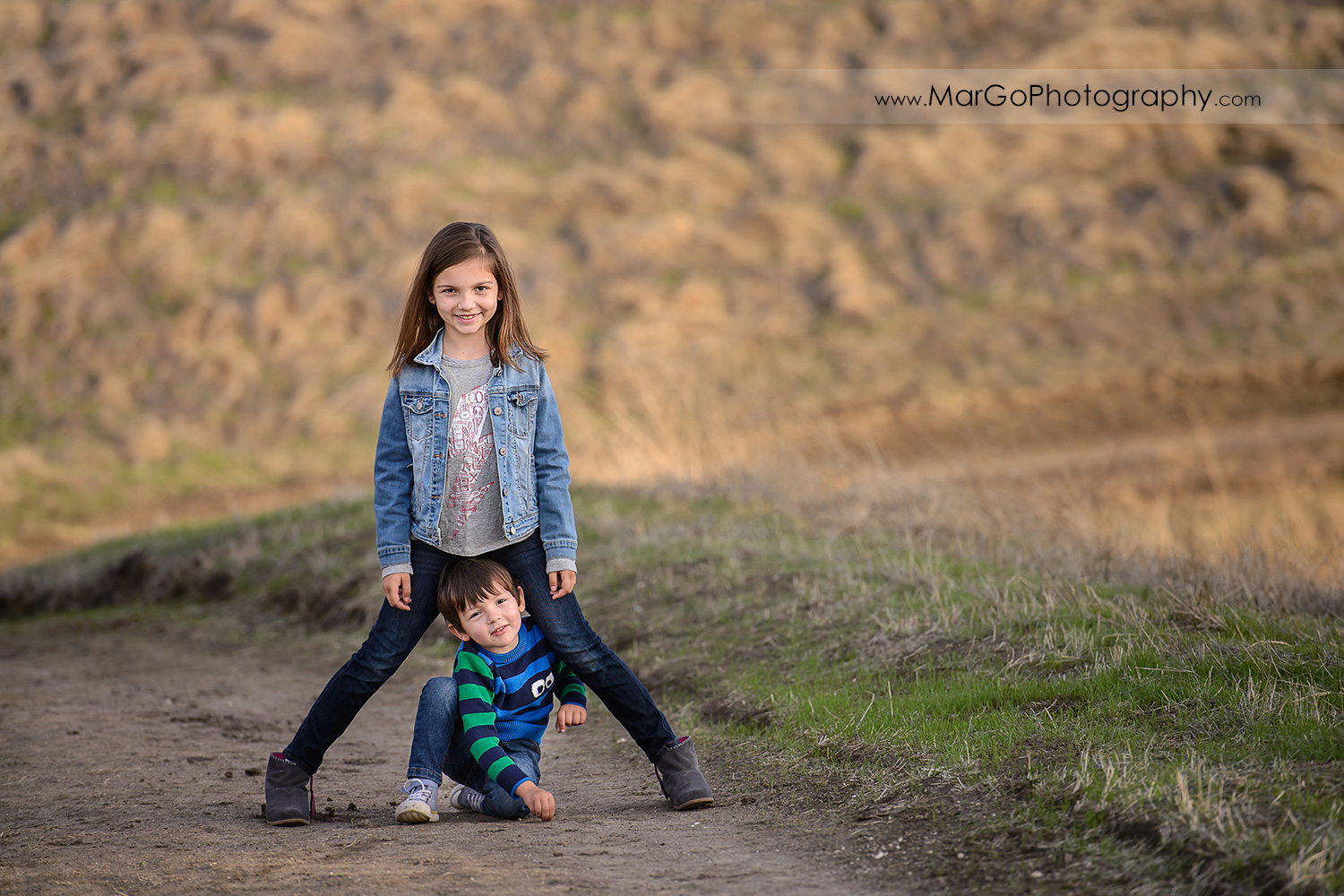 young girl standing over little boy during family session at Diablo Foothills Regional Park in Walnut Creek