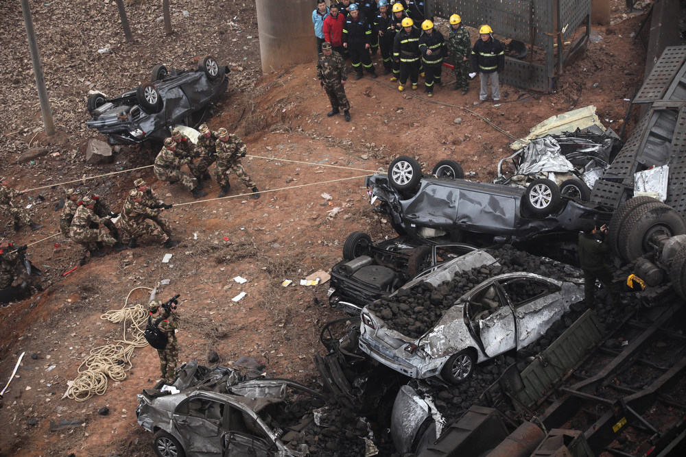 Description of . Rescuers try to move a car at the scene of the collapsed Yichang bridge near the city of Sanmenxia, central China's Henan province, on February 1, 2013 after a fireworks-laden truck exploded as it crossed the bridge killing 26 people as the structure collapsed and vehicles plummeted to the ground, state-run media reported. An 80-meter long part of the bridge collapsed and six vehicles had been retrieved from the debris, China's official news agency Xinhua said. The bridge near the city of Sanmenxia is on the G30 expressway, the longest road in China, which stretches for nearly 4,400 kilometers (2,700 miles) from China's western border with Kazakhstan to the eastern Yellow Sea.      AFP PHOTO  STR/AFP/Getty Images