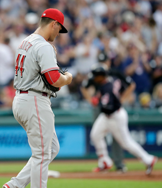 . Cincinnati Reds relief pitcher Tanner Rainey, left, waits for Cleveland Indians\' Jose Ramirez to run the bases after Ramirez hit a three-run home run in the third inning of a baseball game, Wednesday, July 11, 2018, in Cleveland. (AP Photo/Tony Dejak)
