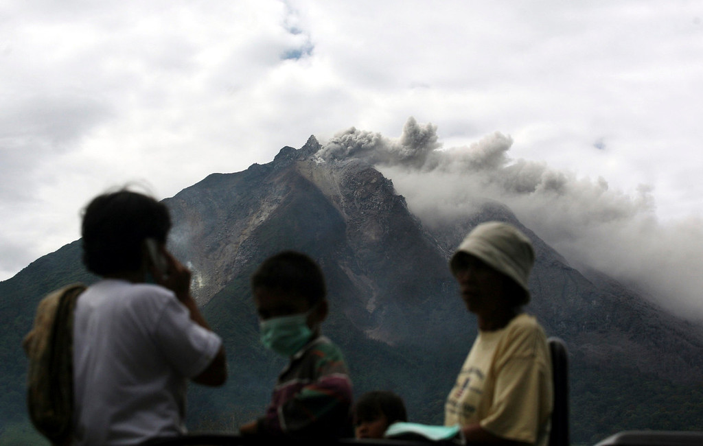 . Mount Sinabung spews volcanic materials as villagers board a truck to flee their homes following its eruption in Karo, North Sumatra, Indonesia, Sunday, Sept. 15, 2013. Thousands of people have been evacuated from their homes after the volcano erupted early Sunday.    (AP Photo/Binsar Bakkara)