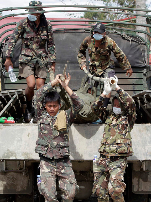 . Soldiers unload a body bag, containing the body of their comrade who drowned during flashfloods at the height of Typhoon Bopha, from an army truck in New Bataan town in Compostela Valley, southern Philippines December 8, 2012.  Philippine President Benigno Aquino declared a state of national calamity on Saturday, four days after this year\'s strongest typhoon left nearly 1,000 people dead or missing mostly in the country\'s resource-rich south. REUTERS/Erik De Castro