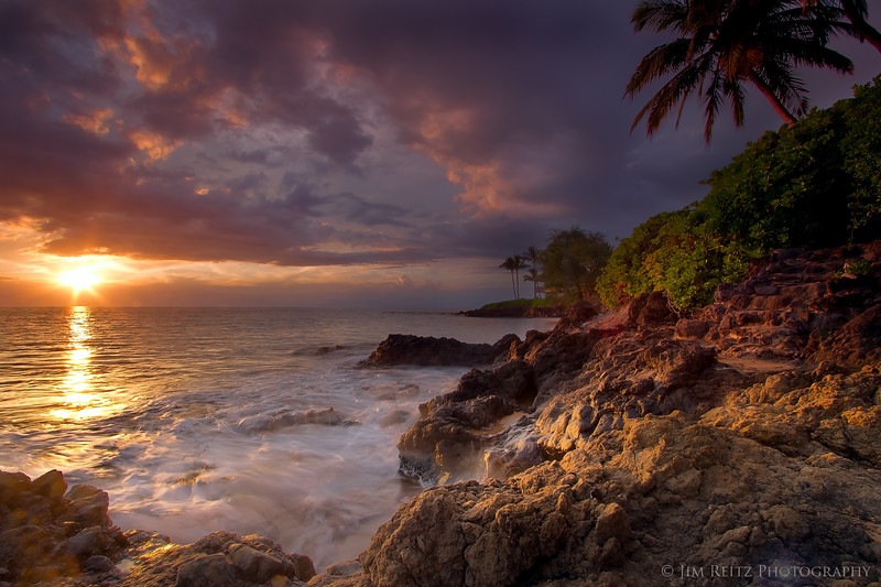 A quick appearance by the sun between cloud banks lights up the rocks near Po'olenalena beach in Maui.