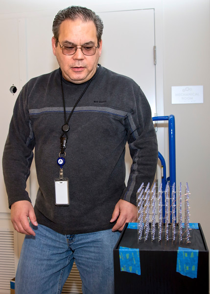 Chris Biddle installs his LED sculpture in the Community Room at WAL. (Photo by Joan Cusick)