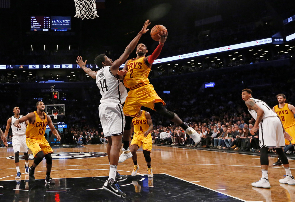 . Brooklyn Nets center Henry Sims (14) blocks Cleveland Cavaliers guard Kyrie Irving (2) as Irving goes up for a layup in the second half of an NBA basketball game, Thursday, March 24, 2016, in New York. The Nets beat the Cavaliers 104-95. (AP Photo/Kathy Willens)