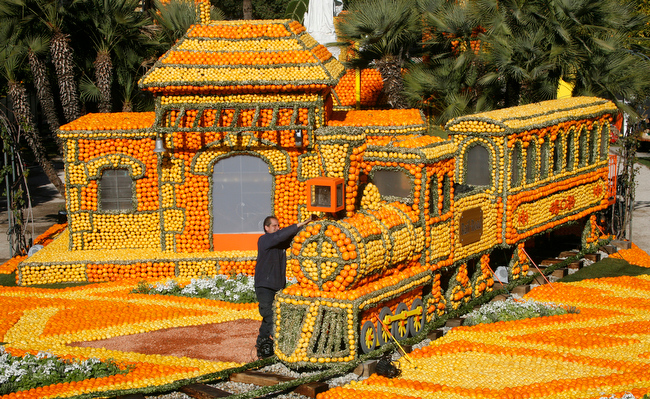 """. A worker puts the finale touch to a train made with lemons and oranges during the 80th Lemon festival in Menton, southern France, Friday, Feb. 15, 2013. The theme for the festival, which involves over 300 professionals working on the project and 145 tons of citrus fruits is \""""Around the World in 80 Days.\"""" (AP Photo/Lionel Cironneau)"""