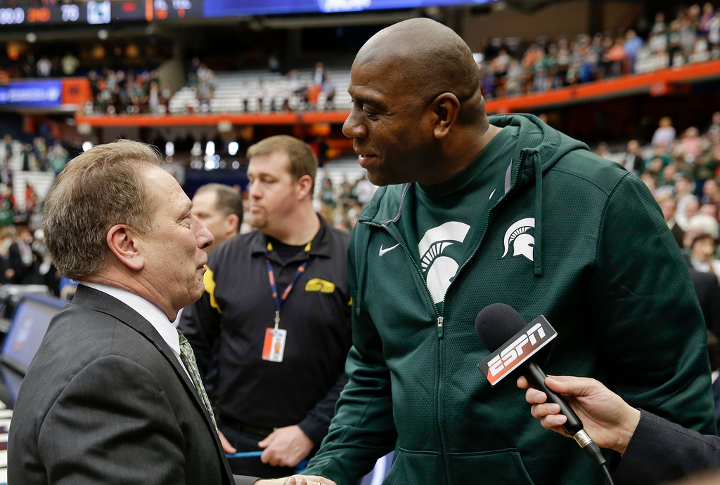 . Magic Johnson, right, congratulates Michigan State head coach Tom Izzo, left, after the east regional final against Louisville in the NCAA men\'s college basketball tournament Sunday, March 29, 2015, in Syracuse, N.Y. Michigan State won the game 76-70. (AP Photo/Seth Wenig)