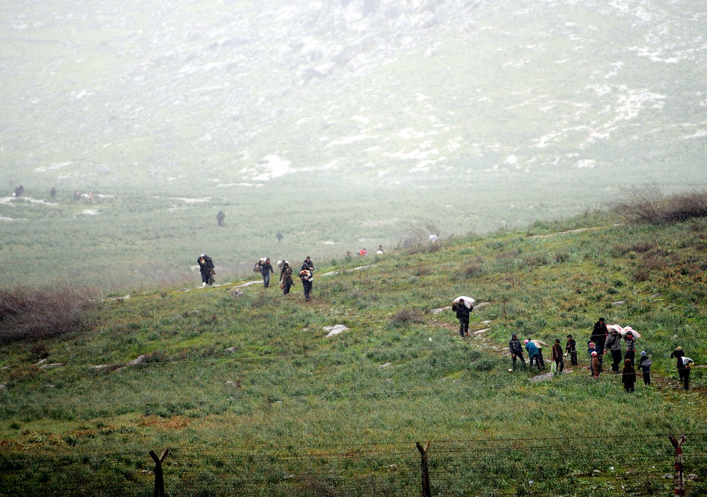 """. Syrian refugees walk across a feild on the Syrian side of the border before crossing into Turkey at Reyhanli in Antakya, on March 14, 2012. International mediator Kofi Annan called for an immediate halt to the killing of civilians in Syria as he arrived in Turkey for talks on the crisis. Activists said that the Syrian army launched a new assault in the restive northern province of Idlib and the city itself, where residents are suffering \""""indescribable\"""" humanitarian conditions. BULENT KILIC/AFP/Getty Images"""