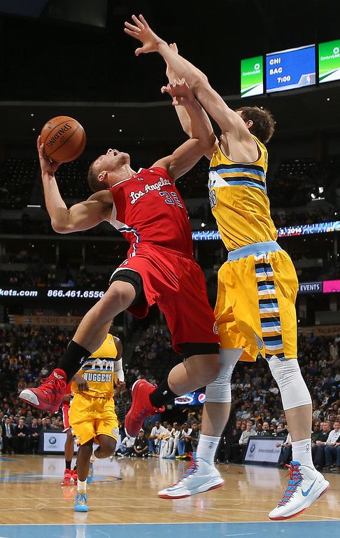 . Los Angeles Clippers forward Blake Griffin, left, is fouled by Denver Nuggets center Timofey Mozgov in the first quarter of an NBA basketball game in Denver, Monday, Feb. 3, 2014. (AP Photo/David Zalubowski)