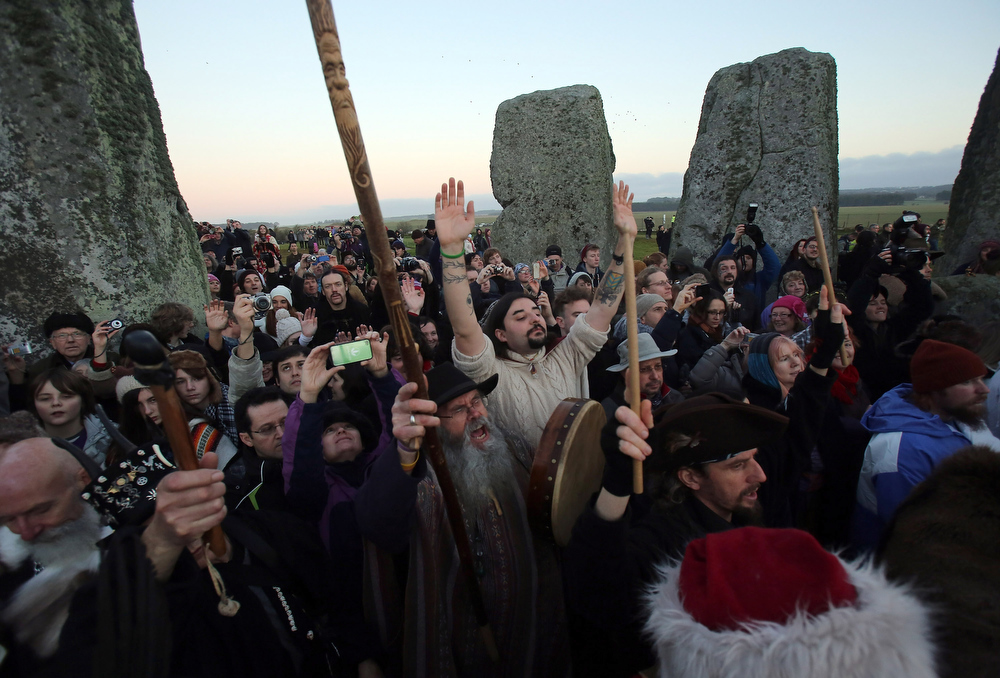 Description of . People cheers as the sun rises as druids, pagans and revellers celebrate the winter solstice at Stonehenge on December 21, 2012 in Wiltshire, England. Predictions that the world will end today as it marks the end of a 5,125-year-long cycle in the ancient Maya calendar, encouraged a larger than normal crowd to gather at the famous historic stone circle to celebrate the sunrise closest to the Winter Solstice, the shortest day of the year.  (Photo by Matt Cardy/Getty Images)