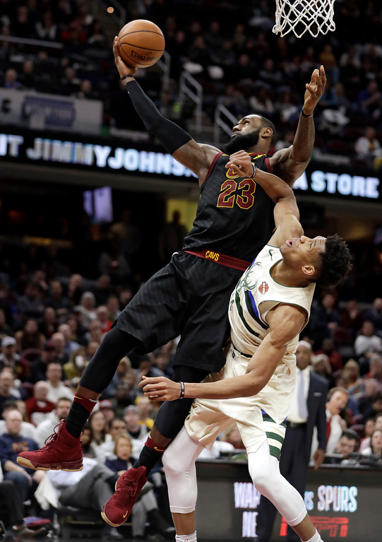 . Cleveland Cavaliers\' LeBron James, left, grabs a rebound ahead of Milwaukee Bucks\' Giannis Antetokounmpo, from Greece, in the second half of an NBA basketball game, Monday, March 19, 2018, in Cleveland. (AP Photo/Tony Dejak)