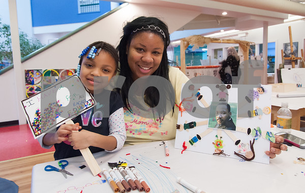 01/15/18 Wesley Bunnell | Staff Imagine Nation held special programs on Monday in honor of Martin Luther King Jr including making peaceful signs, banners and readings on MLK. Chance Simmons, age 5, and mom Charice Gaines hold up their signs they made honoring Dr. King.