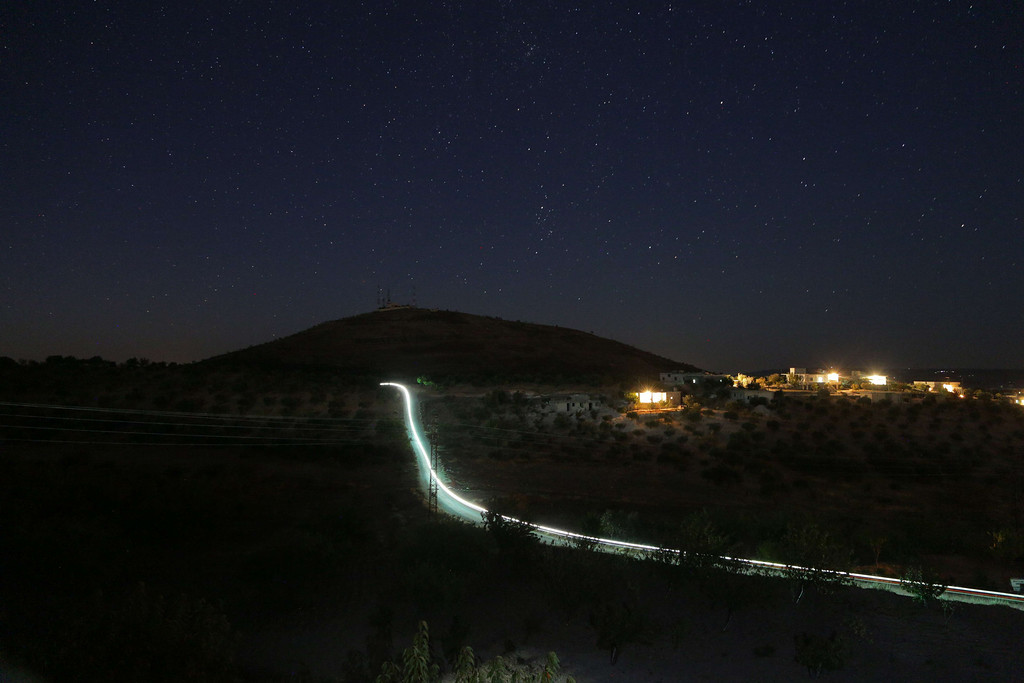 . A picture taken with a long exposure shows the light of a motorcycle as it drives along a road in the Jabal al-Zawiya region of Syria\'s northwestern province of Idlib on October 8, 2013.  MEZAR MATAR/AFP/Getty Images